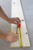 Carpentry. Carpenters hands measuring a wood plank with measuring tape and pencil Stock Images
