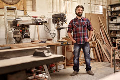 Carpentry business owner standing in his workshop with machinery Stock Photos