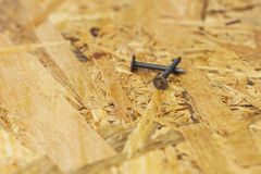 Carpentry concept. Close up of nails on wooden board Stock Photos
