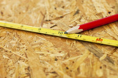 Carpentry concept. Close up pencil and measure tape on wooden board Royalty Free Stock Photo