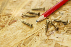 Carpentry concept. Close up of pencil and screws on wooden board Royalty Free Stock Photography
