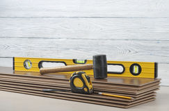 Carpentry concept.Different tools- level,tape-measure,rubber hammer on the new laminate flooring.Copy space for text. Stock Image