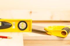 Carpentry concept: a saw and a bubble level Stock Photos