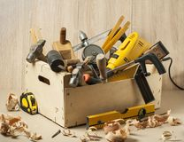 Carpentry concept.Wooden box with many carpentry tools on workplace.