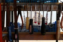 Old tools hanging on a worker`s shelf. Screwdrivers, hammer and pliers. royalty free stock images