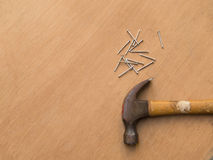 Carpentry, hammer and nails on wooden board Stock Photo