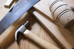 Carpentry hammers and saw. Over wood table Royalty Free Stock Images