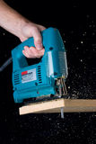 Carpentry - Jigsaw. Jigsaw cutting through a pine board Stock Photos