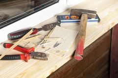 Carpentry Level And Tools. Carpentry level and hand tools laid on the wooden window sill Stock Photo