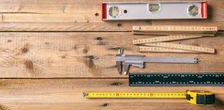 carpentry Meça a fita, o nível de espírito e as réguas no fundo de madeira, espaço da cópia, vista superior fotografia de stock royalty free