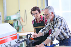 Carpentry professor teaching young woman apprentice Royalty Free Stock Photography