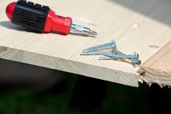 Carpentry: screwdriver, screws and wood planks Stock Photo