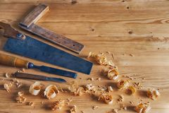 Carpentry tools concept. Vintage equipment for working with wood. planer, saw and chisel on wooden table with shavings Stock Photo