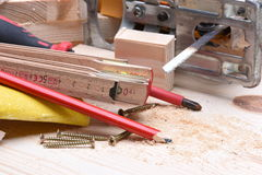 Carpentry tools and electric jigsaw on wooden board Stock Image