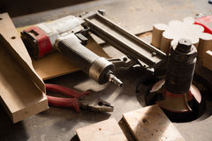Carpentry tools - gun nailing and pliers on a workbench. Carpentry tools - gun nailing and pliers lie on a workbench Royalty Free Stock Photo