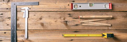 Carpentry. Measure tape, spirit level and rulers on wooden background, banner, copy space, top view. Carpentry tools. Measure tape, spirit level and rulers on stock photo