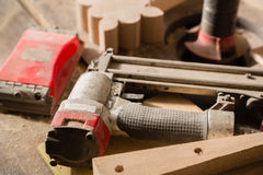 Carpentry tools - nailing gun and sander on workbench Stock Photography