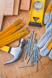 Carpentry tools nails claw hammer protective gloves level planks Stock Images