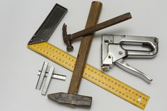 Carpentry tools on a white background. Hammer, gon, stapler and staples to him on a white background Royalty Free Stock Photos