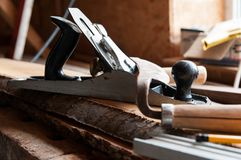 Carpentry tools on wood boards, focus on the plane. In a little workshop royalty free stock photos