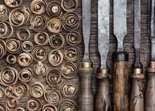 Carpentry tools on the workbench. Set of used professional carving tools on the workbench and wood shavings close up: carpentry, craftsmanship and handwork Royalty Free Stock Photos
