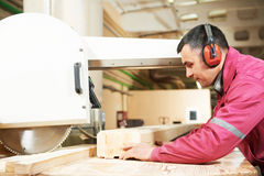 Carpentry worker cutting wood cross beam Royalty Free Stock Images