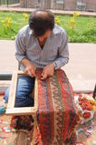 Carpet. A man making carpet by knitting ropes Stock Images