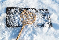 Carpet beater over carpet with snow for winter cleaning.  Royalty Free Stock Image