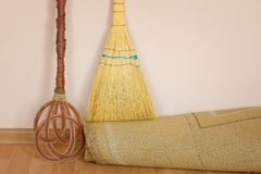Carpet beater, straw broom and carpet. Indoors Stock Image