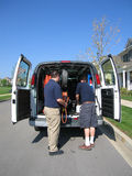 Carpet Cleaners Unload Van. A professional carpet cleaning team unloads their vacuum and supplies Stock Photos