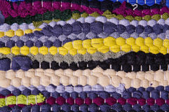 Carpet of colored rags. Cheap carpet made by assembling scraps of new fabric and used tissues. The recycling of used objects and materials is one of the Royalty Free Stock Images