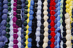 Carpet of colored rags. Cheap carpet made by assembling scraps of new fabric and used tissues. The recycling of used objects and materials is one of the Royalty Free Stock Photos