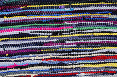 Carpet of colored rags. Cheap carpet made by assembling scraps of new fabric and used tissues. The recycling of used objects and materials is one of the Royalty Free Stock Image