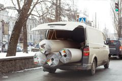 Carpet delivery van with open trunk. Large bulky cargo transportation. Carpeting cleaning and delivery concept.  royalty free stock photo