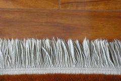 Carpet Fringe. The fringe of a carpet on hardwood floor stock images