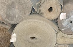 Carpet by the roll. Warehouse has rolls of earthtone carpet laying in stacks.  Blank roll tags hang from several rolls Stock Photography