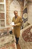 Carpet seller offering colorful oriental carpets at his store Royalty Free Stock Photos