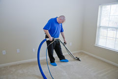 Carpet steam cleaning. Man cleaning carpet with commercial cleaning equipment
