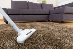 Carpet with vacuum cleaner in living room Stock Images