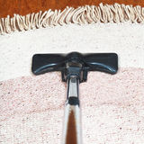 Carpet vacuuming with a hoover Royalty Free Stock Images