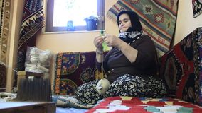 Carpet weaving. Aged turk woman with silk clew