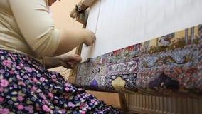 Carpet weaving. Turk woman making a silk carpet Royalty Free Stock Images