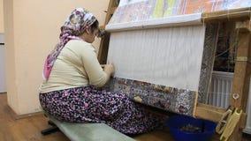 Carpet weaving. Turk woman making a silk carpet Royalty Free Stock Image