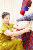 Carpet weaving woman sideview closeup Stock Photography