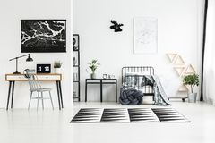 Carpet between workspace and bedroom. Black and white carpet between wooden workspace with laptop and bright bedroom with knot pillow Royalty Free Stock Image