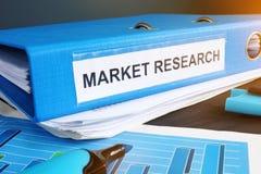 Carpeta azul con un estudio de mercados de la etiqueta fotografía de archivo