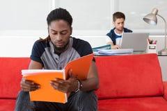 Carpeta casual de la lectura del hombre joven en oficina foto de archivo libre de regalías