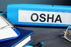 Carpeta con la Occupational Safety and Health Administration OSHA de la etiqueta imagenes de archivo