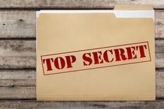 Carpeta con las palabras descoloradas de alto secreto en de madera fotos de archivo libres de regalías