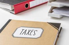 Carpeta con los impuestos de la etiqueta foto de archivo libre de regalías